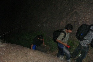 Climbing up the rocky hill in torchlight.